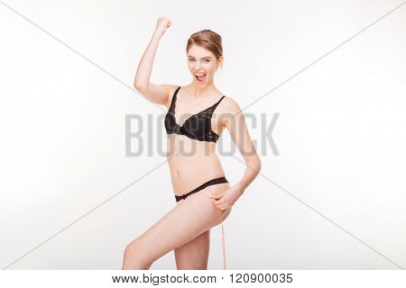 Excited happy young woman in black lingerie celebrating success and measuring her hips over white background