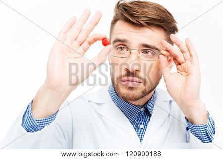Young male doctor in glasses looking on pill isolated on a white background