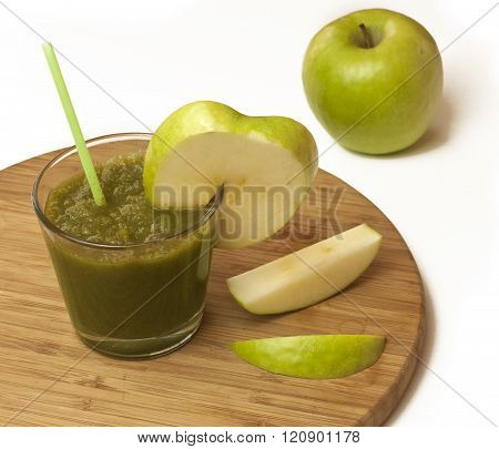 A glass of apple smoothie with a drinking straw, with a wedge of an apple and apple slices