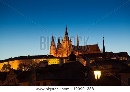 Twilight scene of Prague and St Vitus cathedral and castle in the distance.