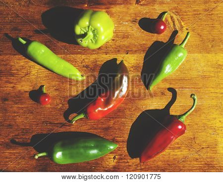 Red and green peppers on wooden table
