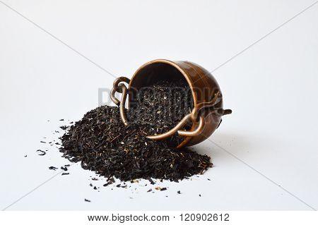 Copper pot with half-spilled black tea