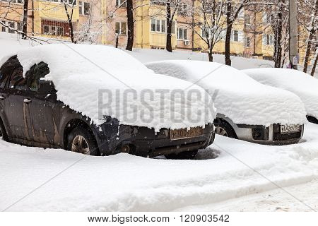 Vehicles Covered With Snow In The Winter Blizzard In The Parking Lot