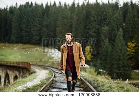 a bearded young man on the railway tracks