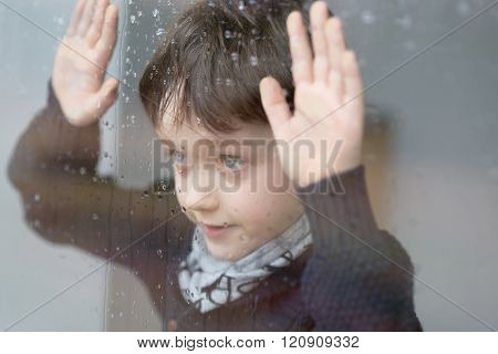 Young 7 Years Old Boy Standing Beside The Window