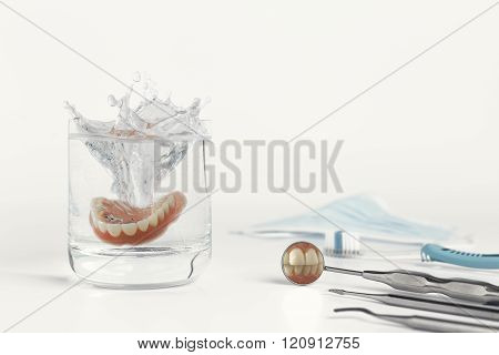 Teeth on mirror next to dentures in water