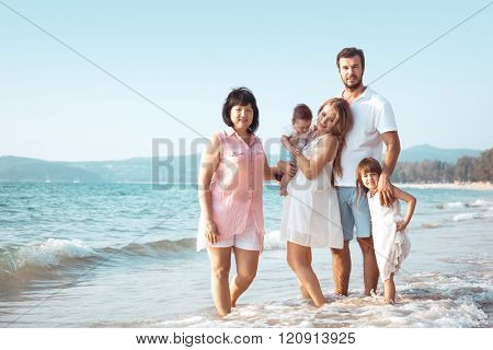 Family walking on the evening beach during sunset. Children with parents and grandma.