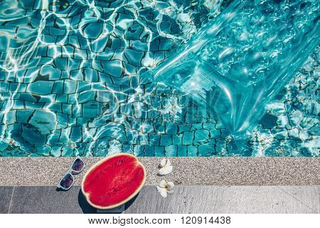 Watermelon, sunglasses and floating mattress the blue pool. Tropical fruit diet. Summer holiday idyllic.