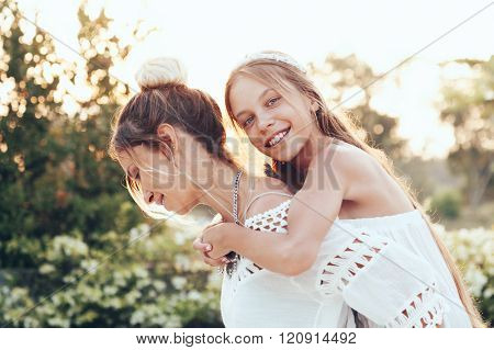 Tween daughter hugging with her mom in summer sunlight