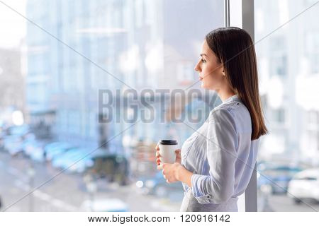 Pleasant sad woman standing near window