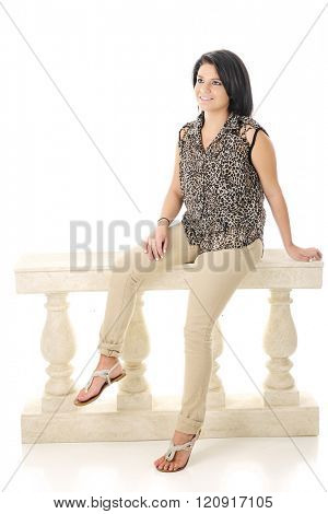 A beautiful teen girl happily looking up while sitting on a balustrade.  On a white background.