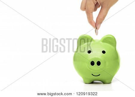 hand putting a golden coin to a green piggy bank - people do green saving