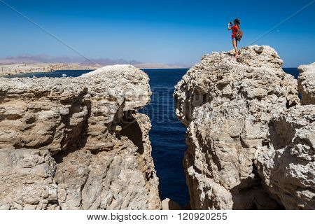 Young lady taking picture from top of the cliff in the National Park of Ras Muhammad, Egypt