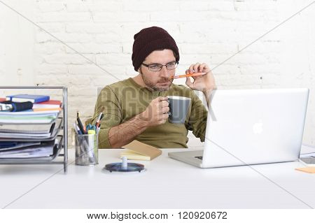 young hipster businessman working from his home office as freelancer wearing casual beanie and glasses looking busy in self employed business model success