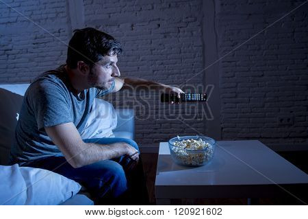 young happy television addict man sitting on home sofa watching TV eating popcorn using remote control zapping while enjoying movie sitcom or live sport at night