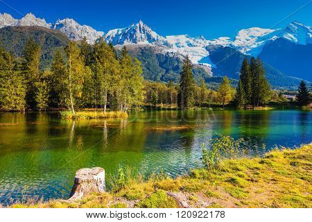 City Park is illuminated by sunset.  The mountain resort of Chamonix, Haute-Savoie. The lake reflected the snow-capped Alps and evergreen spruce
