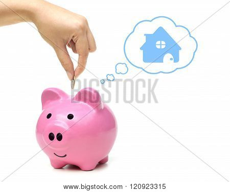 hand putting a coin into a pink piggy bank thinking of buying a new house - saving money for future concept