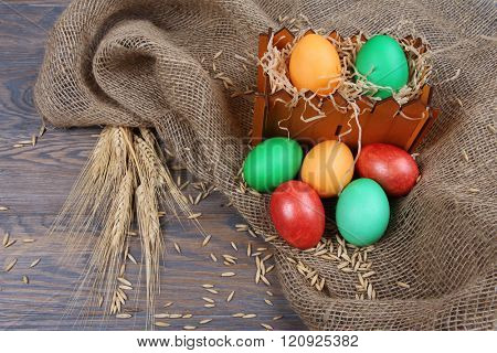 Rustic background with Easter eggs and wheaten ears on sackcloth
