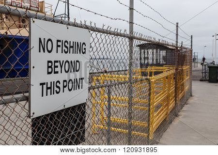 No Fishing Beyond This Point Sign On Mesh Fence