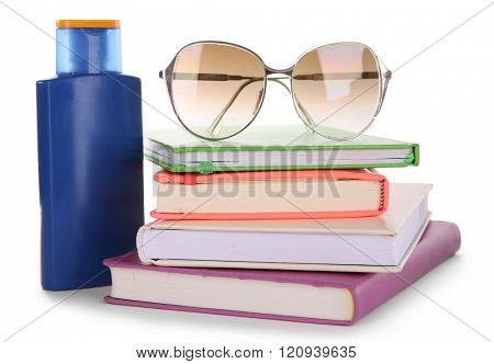 Travel set: books, glasses and suntan oil, isolated on white