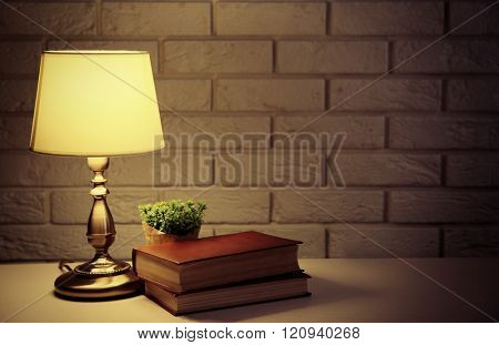 Night lamp and books on the desk on white brick wall background