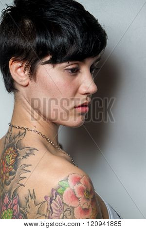 Rear View Of A Beautiful Short-hair Brunette Woman With A Tattoo At Back.