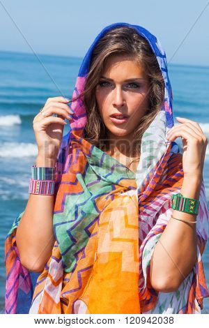 tanned young beach fashion woman portrait with  colorful sarong and bracelets  at sea beach sunny summer day