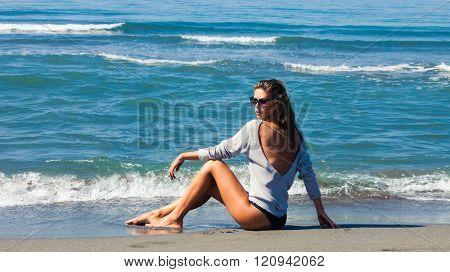fashion girl in bikini and tunic  on sandy sunny sea beach, full body shot side view