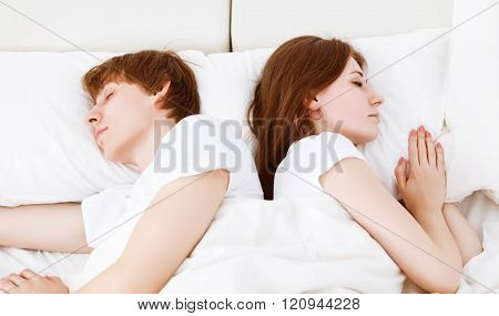 Upset Couple Having Marital Problems A Disagreement And Sleeping  In Bed