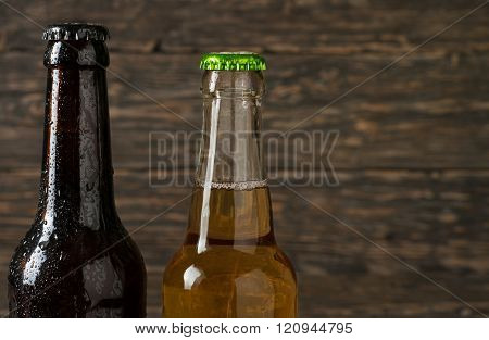 dark beer bottle and bottle of ale on dark wooden background