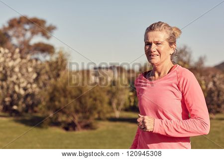 Athletic senior woman running outdoors in sporty top
