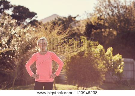 Active senior woman wearing sporty top in morning sunlight