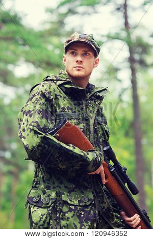 hunting, war, army and people concept - young soldier, ranger or hunter with gun in forest
