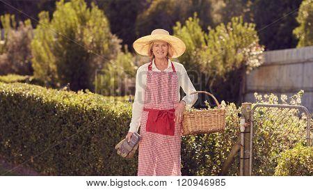 Senior woman in gardening gear at her backyard gate