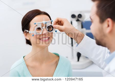 health care, medicine, people, eyesight and technology concept - optometrist with trial frame checking patient vision at eye clinic or optics store