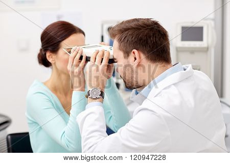 health care, medicine, people, eyesight and technology concept - optometrist with pupilometer checking patient intraocular pressure at eye clinic or optics store