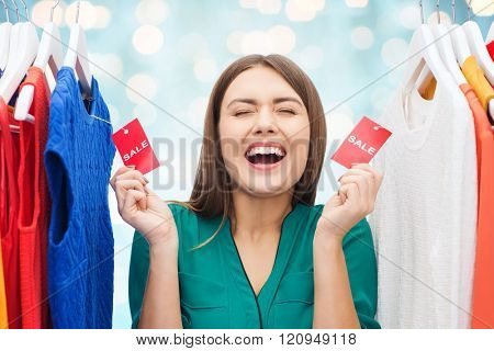 clothing, fashion, sale, shopping and people concept - happy woman showing tags on clothes at wardrobe over blue holidays lights background
