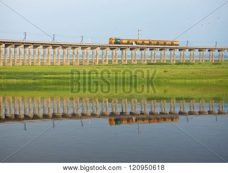 Train on the railway cross grass field with water reflection at Pasuk River Dam in summer, Lopburi,