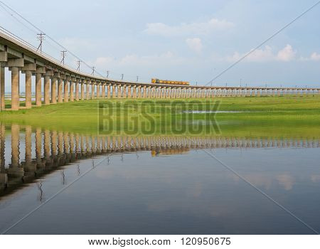 Train On The Railway Bridge With Water Reflection