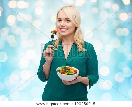 healthy eating, food, diet and people concept - smiling young woman eating vegetable salad with fork over blue holidays lights background
