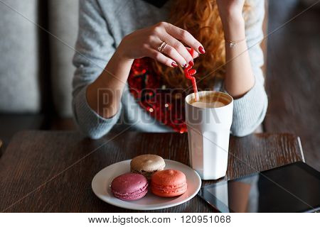 Young woman with red curly hair,and this spends time at a table in a café,stirs sugar in the white Cup of cappuccino coffee,red nail Polish,on the table is a white plate with multi colored French vanilla cookies