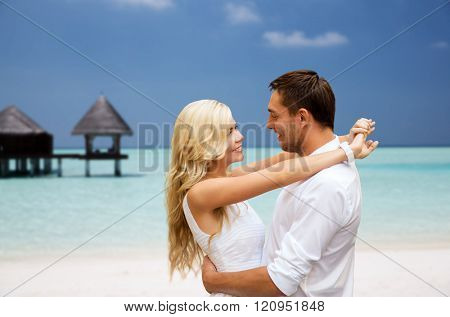 summer holidays, tourism, vacation, travel and dating concept - happy couple having fun at sea side over beach with bungalow background