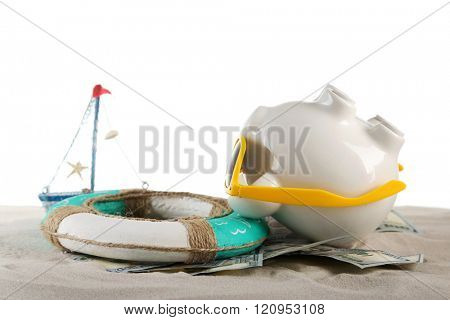 Piggy bank with dollar banknotes, sunglasses and lifebuoy on a sand, isolated on white. Holiday money concept