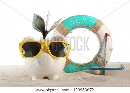 Piggy bank with inserted dollar banknotes, sunglasses and lifebuoy on a sand, isolated on white. Holiday money concept