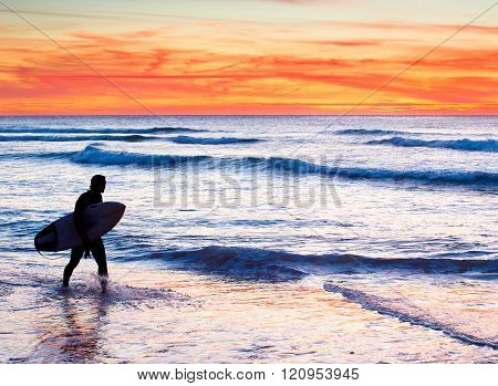 Unidentified surfer with surfboard in the ocean at sunset