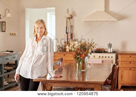 Senior woman standing in a rustic style tidy kitchen