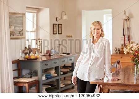 Senior woman looking relaxed in her bright rustic kitchen