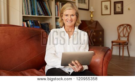 Smiling senior woman in living room with digital tablet