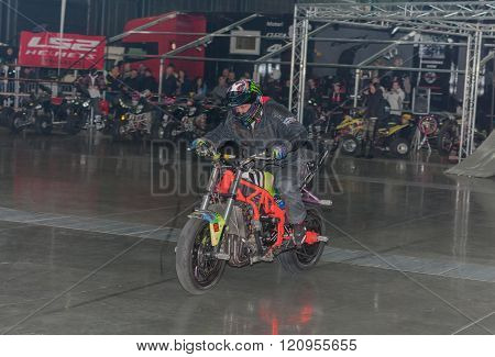 Stuntman riding a motorcycle during stunt show