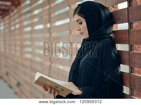 Emarati Arab Woman Outside Reading A Book